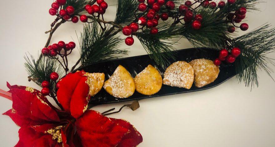 piccoli dolci ripieni a forma di raviolo che vengono fritti e serviti con una spolverata di zucchero a velo.